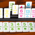 Card rack in rummy card game close up playing on wooden board Stock Image