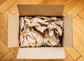 Cardboard box from above filled with shipping packaging paper on a wood floor seen directly freight transportation and e commerce Royalty Free Stock Image