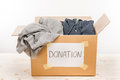 Cardboard box with donation clothes on wooden table on white
