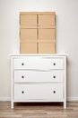 Cardboard boxes on white wooden commode