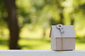 Cardboard house with key against green bokeh. Building, loan, housewarming, insurance, real estate or buying new home. Royalty Free Stock Photo