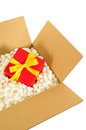 Cardboard shipping box, small red christmas gift inside, styrofoam polystyrene packing pieces Royalty Free Stock Photo