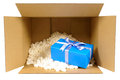Cardboard shipping delivery box with blue gift inside and polyst Royalty Free Stock Photo