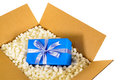 Cardboard shipping delivery box blue gift inside and polystyrene packing pieces Royalty Free Stock Photo