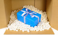 Cardboard shipping delivery box with blue gift inside and polystyrene packing pieces, front view Royalty Free Stock Photo