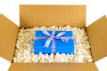 Cardboard shipping delivery box with blue gift inside and polystyrene packing pieces, top view Royalty Free Stock Photo