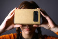 Cardboard virtual reality color shot of a young woman looking through a a device with which one can experience on a mobile phone Stock Photography