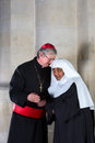 Cardinal and nun catholic talking in a medieval church Royalty Free Stock Photo