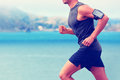 Cardio runner running listening smartphone music unrecognizable body jogging on ocean beach or waterfront working out with heart Stock Photography