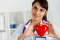 Cardiology care health protection and prevention beautiful smiling female doctor holding red heart in front of chest closeup Royalty Free Stock Photos