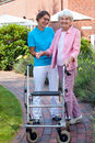 Care assistant helping an elderly lady as they take a walk together in the garden of old age home using a walker Stock Photo