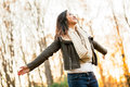 Carefree asian woman at the park young in mid s with arms outstretched on an autumn late afternoon Stock Image