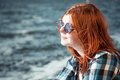 Carefree beautiful red hair young woman over seascape in sunglasses Royalty Free Stock Image