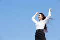 Carefree business woman arms up and feel free isolated on blue sky background asian beauty Stock Photos