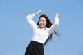 Carefree business woman arms up and feel free isolated on blue sky background asian beauty Stock Images