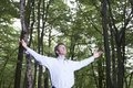 Carefree businessman standing alone in forest with arms outstretched Stock Photography