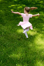 Carefree child dancing a little ballerina in pink dances her way through her back yard a that will always be and young at heart Royalty Free Stock Images