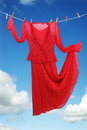 Carefree clothing red dress hanging and dancing on a clothesline against blue sky concept for freedom and romance Stock Photography