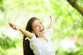 Carefree elated cheering woman in spring or summer forest park full of hope and vitality multiracial girl raising her arms up Royalty Free Stock Image
