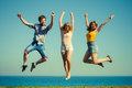 Carefree friends jumping by sea ocean water. Royalty Free Stock Photo