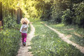 Carefree happy childhood with playful child walking alone on rural footpath in forest during summer holidays Royalty Free Stock Photo
