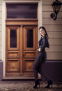 Carefree lovely woman walking on the street pretty smiling dressed in black with high heel shoes old town building wall as Stock Photo