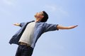 Carefree man and free raised hands and looking to a sky asian Royalty Free Stock Photo