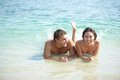Carefree time portrait of a smiling couple lying in warm water and looking at camera Stock Images
