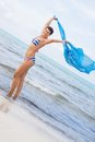 Carefree woman on a beach with a floating scarf beautiful young in bikini running and leaping pretty turquoise blue out in the Stock Images