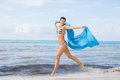 Carefree woman on a beach with a floating scarf beautiful young in bikini running and leaping pretty turquoise blue out in the Royalty Free Stock Image