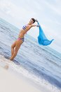 Carefree woman on a beach with a floating scarf beautiful young in bikini running and leaping pretty turquoise blue out in the Royalty Free Stock Photo