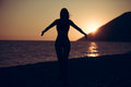 Carefree woman dancing in the sunset on the beach.Vacation vitality healthy living concept.Free woman enjoying freedom feeling hap Royalty Free Stock Photo