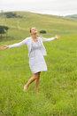 Carefree woman grassland beautiful young arms open in Royalty Free Stock Images