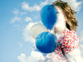 Carefree woman holding balloons outdoors against summer blue sky Stock Images