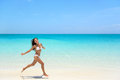 Carefree woman jumping on beach during summer young with arms outstretched sea shore full length of exhilarated female in white Stock Image