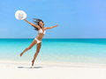 Carefree woman jumping at beach during summer young vacation full length of exhilarated female in white bikini tourist with arms Stock Image