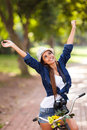 Carefree woman outdoors young arms open on her bike Royalty Free Stock Photos