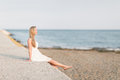 Carefree woman relaxing at the seaside beautiful young blond sitting on a stone wall kicking her bare feet in air Stock Images