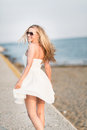 Carefree woman on a summer beach beautiful blond wearing white dress and sunglasses walking away from the camera walkway Royalty Free Stock Image