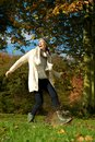 Carefree woman walking in the park and kicking a puddle of water portrait with boots Stock Photo