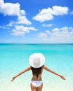 Carefree woman in white hat and bikini on beach standing with arms outstretched against turquoise sea blue sky rear view of female Stock Photo