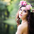 Carefree young fashion woman with curly windy hair outdoors girl on greenery background Royalty Free Stock Photos