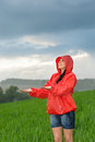 Carefree young girl enjoying rainy weather in raincoat Royalty Free Stock Images