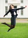 Carefree young woman jumping outdoors portrait of a Royalty Free Stock Photo