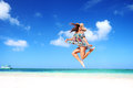 Carefree young woman is jumping into the sky with beautiful fluffy clouds Stock Photos