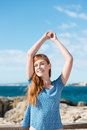Carefree young woman at the seaside beautiful enjoying warm summer sun standing with her arms raised above her head Royalty Free Stock Image
