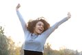 Carefree young woman smiling with arms raised portrait of a Stock Photo