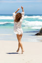 Carefree young woman in summer dress walking on beach full body portrait of a to water Royalty Free Stock Photos