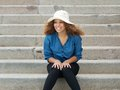 Carefree young woman wearing hat sitting on stairs portrait of a Stock Image