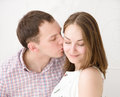 Careful man kissing his girlfriend men smiling Royalty Free Stock Images